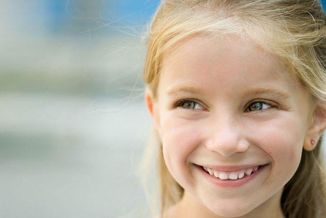 una bambina bionda con capelli biondi lunghi mentre sorride