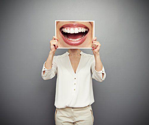 donna con un cartellone di una bocca sorridente in mano