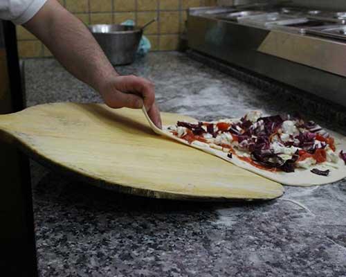 un cuoco mentre appoggia una pizza su una paletta