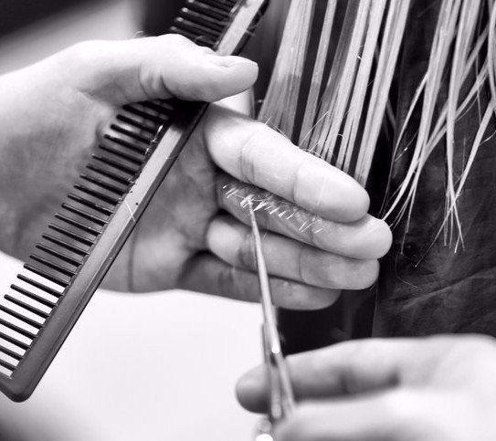 parrucchiere sistema i capelli di una cliente con della lacca