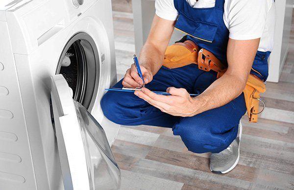 un tecnico che compila una scheda tecnica e accanto una lavatrice
