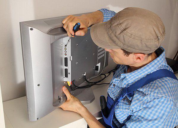 un tecnico con un cacciavite  mentre ripara una tv