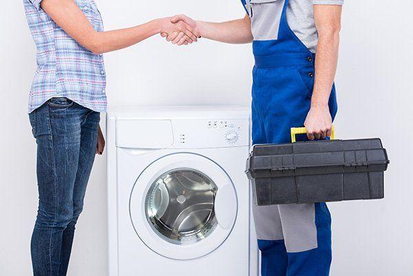 una stretta di mano tra una donna e un tecnico e vicino una lavatrice
