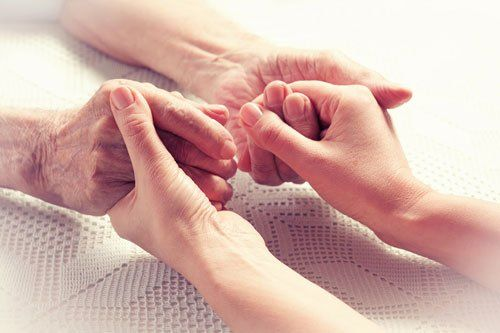 mani di una giovane donna che stringono le mani di un anziano