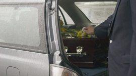 portiera aperta di un carro funebre con bara