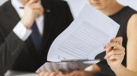 pratica di agibilità, documenti cartacei, due persone che visionano i documenti
