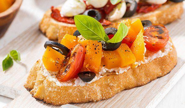 una bruschetta con pomodorini gialli e rossi e basilico