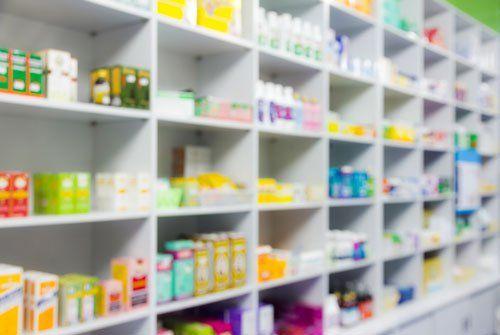 immagine sfocata di uno scaffale bianco a scompartimenti con prodotti farmaceutici esposti