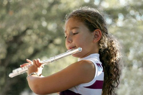 Cute young player playing flute
