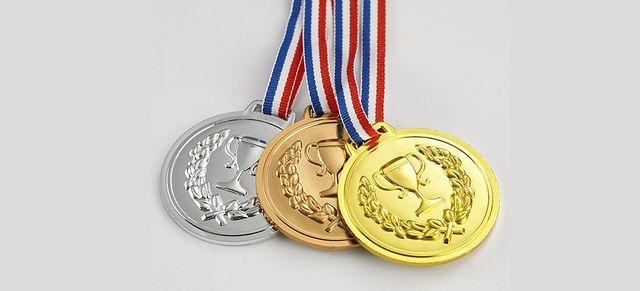 Silver, bronze and gold medals on red, blue and white chains
