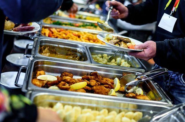 recipienti in metallo in un buffet con del cibo e delle persone che si servono
