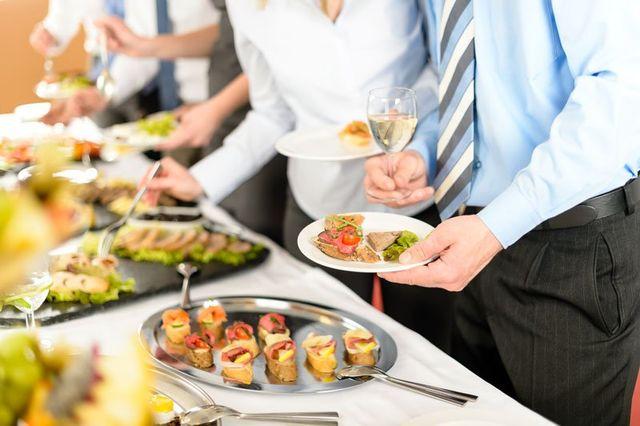 tavola con buffet con del cibo, in piedi un uomo con un bicchiere di vino in mano e un piatto e dietro altre persone che si servono