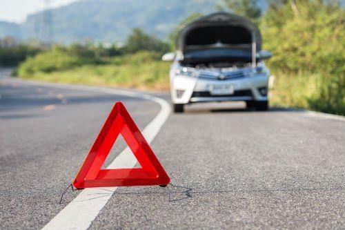 una macchina con il cofano aperto sulla strada con un triangolare rosso davanti