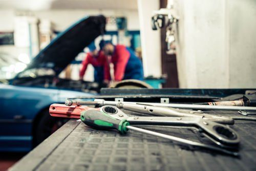 due meccanici che riparano una macchina e vista ravvicinata degli attrezzi