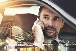 un uomo seduto in macchina al telefono