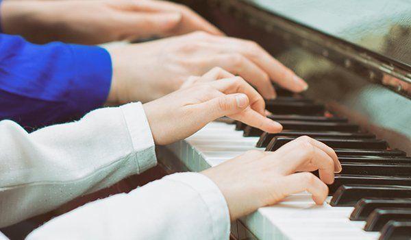 diverse mani che suonano su un pianoforte