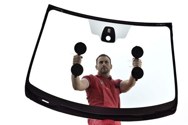 un uomo con due ventose con un manico solleva un vetro anteriore di una macchina