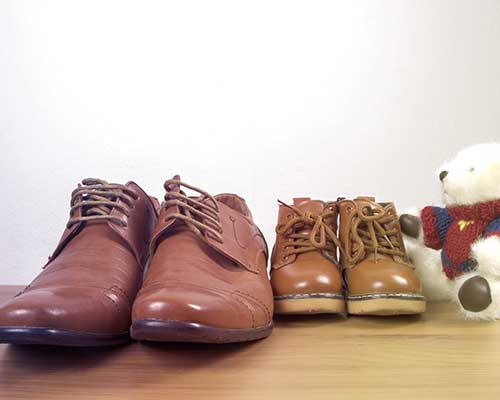 un paio di scarpe da adulto e uno da bambini accanto ad un orsacchiotto