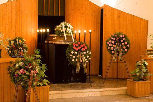 cerimonia funebre con bara e corone di fiori