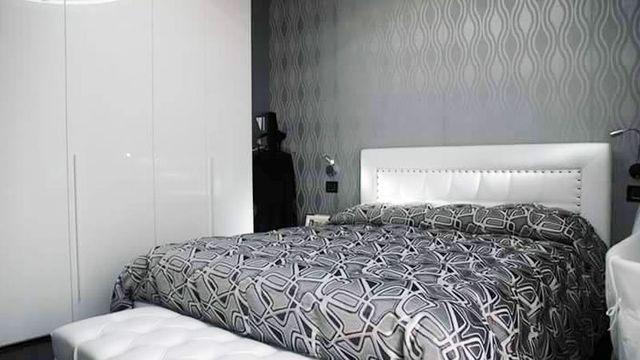 una stanza con un letto matrimoniale con piumone grigio a disegni bianchi e mobili bianchi