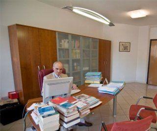 Partner lavorando in suo ufficio ha la tavola piena di libri e dossier