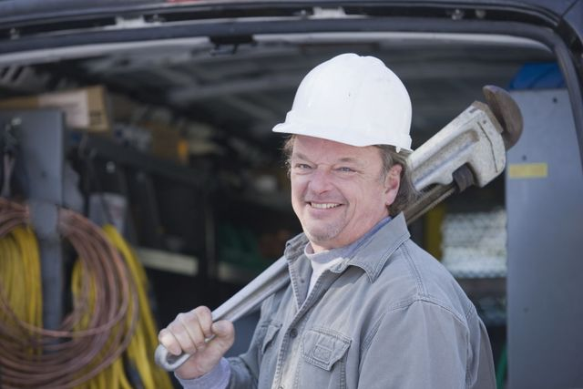 A smiling plumber holding a large wrench