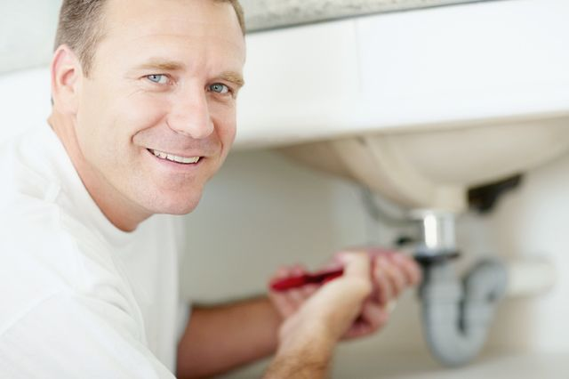 A happy plumber working on a sink