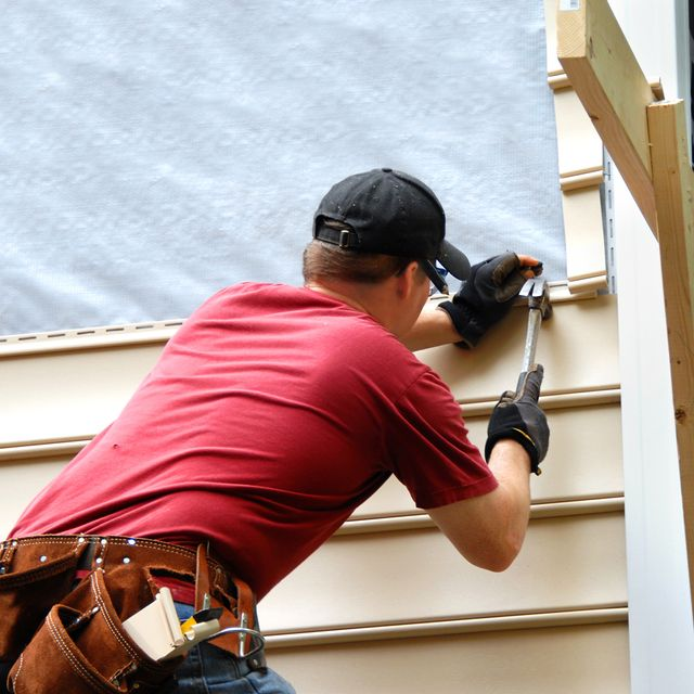 Siding being installed to a home by a worker in a red shirt