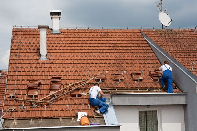 Contractors re-roofing an Auckland property