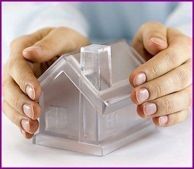 mani che tengono un modellino di casa