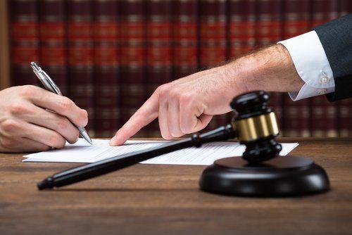 un avvocato mostrando al cliente dove firmare