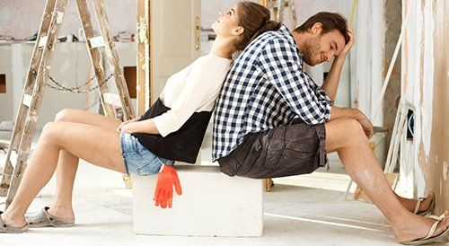 Couple sitting while their house is being renovated in New York, NY