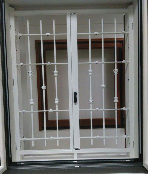 una griglia bianca in ferro battuto di una finestra