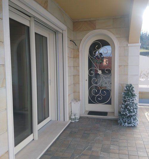 vista dall'esterno delle finestre di una casa e un piccolo albero