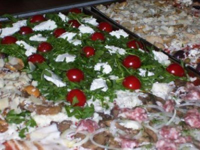una pizza pronta da infornare in una teglia con rucola pomodorini e altri ingredienti