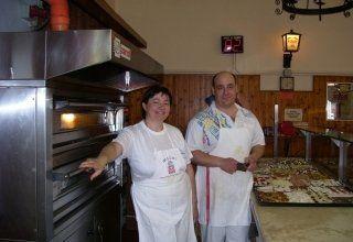 una donna e un uomo con dei grembiuli e vestiti bianchi vicino a un forno