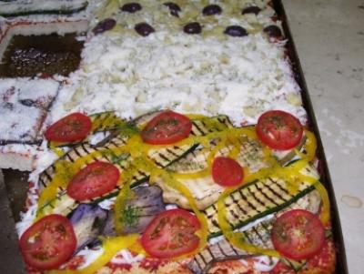 una pizza in teglia pronta da infornare con melanzane peperoni, pomodori e mozzarella