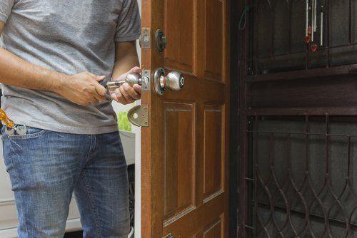 persona che sistema la serratura di una porta