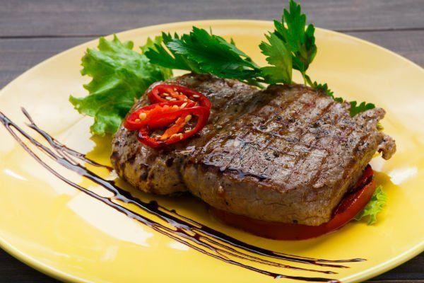 un piatto di carne alla griglia, un peperone rosso e