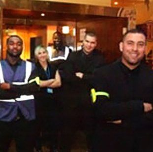 smiling door staff, all with arms folded