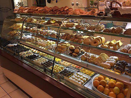 Bancone con vetrina, ricco di  cornetti, cornetti farciti, paste ,pasticcini e dolci vari