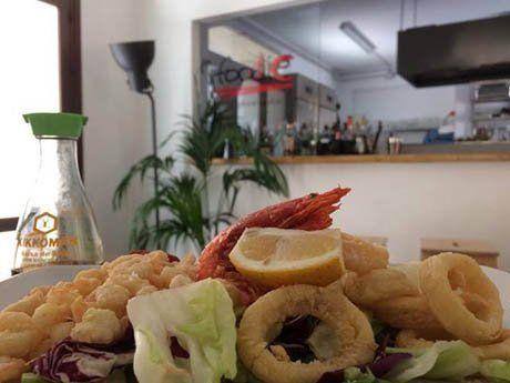 Primo piano di un piatto con calamari ricoperti e gamberetti