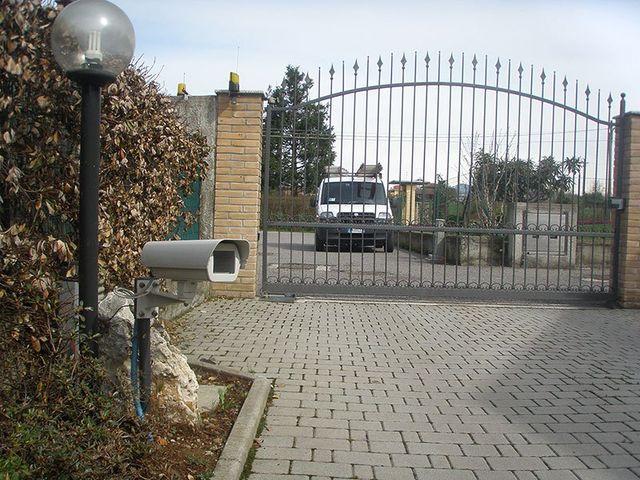 una telecamera di sicurezza installata a basso livello e dietro un cancellone d'entrata con un furgone bianco da lavoro