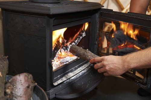 Wooden log being inserted in the fireplace