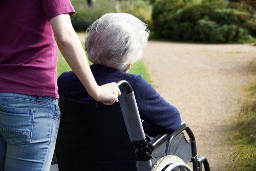 una signora anziana su una sedia rotella e una donna che accompagna