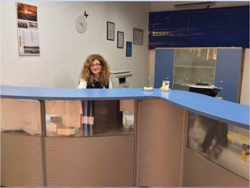 Donna che sorride alla reception di un centro per rinnovo patenti