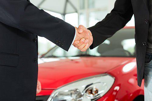 La stretta di mano di due professionisti con sfondo di una macchina rossa