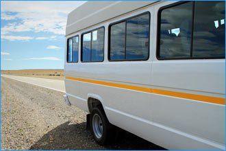 rear of white minibus with yellow stripe