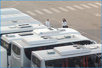 row of white minibuses seen from above