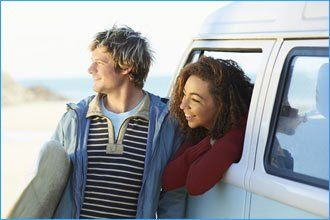 man standing with woman looking out of a white vehicle